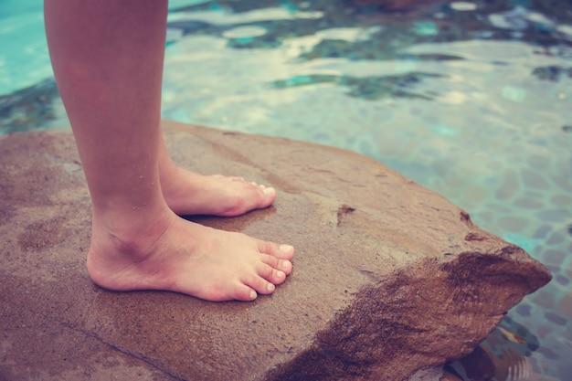 Person, die auf der spitze eines felsens mit blick auf das meer