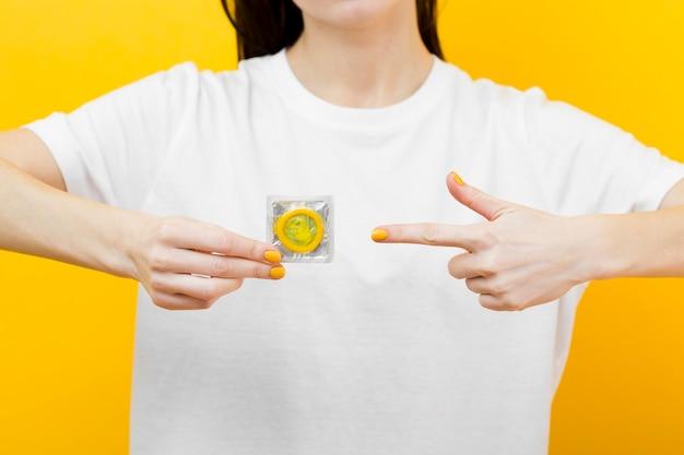 Person, die auf ein gelbes kondom zeigt