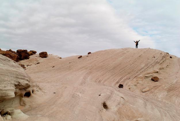 Person, die auf einem felsen mit den armen ausgestreckt steht, amangiri, canyon point, hoodoo-spur, utah, usa
