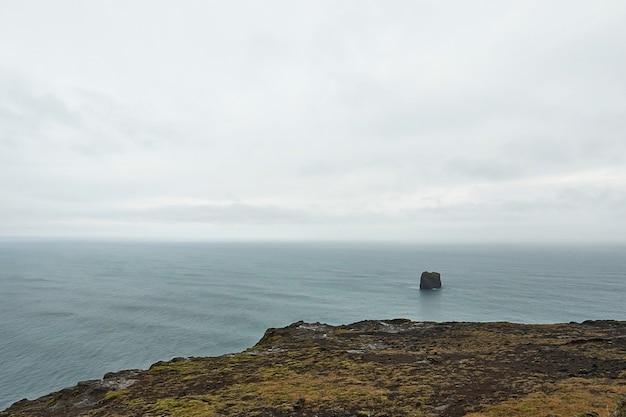 Person, die auf klippe nahe meer unter bewölktem himmel während zeitnatur fantastisches schönes neues schönes foto steht