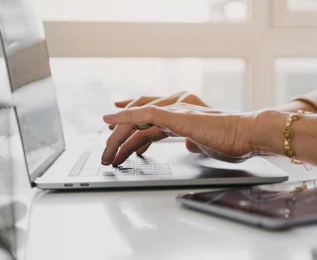 Person, die auf laptoptastatur schreibt