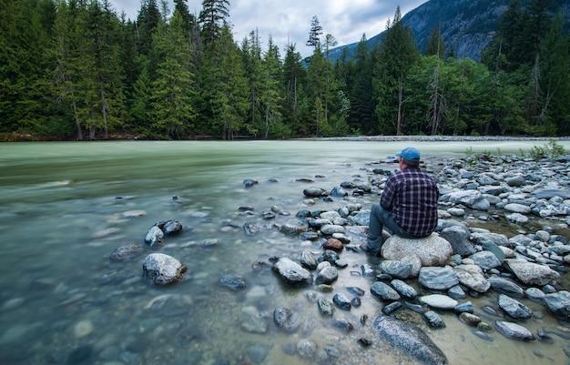 Person, die auf stein nahe dem gewässer sitzt