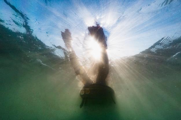 Person, die auf surfbrett im blauen ozean liegt
