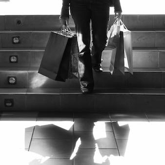 Person, die auf Treppen mit Einkaufstaschen geht
