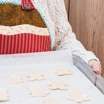 Person, die backblech mit weihnachtsplätzchen holt