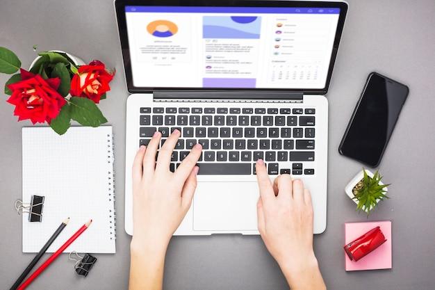 Person, die bei tisch an laptop arbeitet