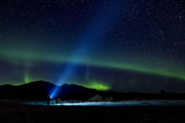 Person, die beleuchtete taschenlampe im dunklen himmel hält
