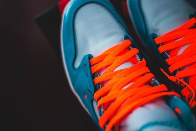 Person, die blaue und orangefarbene niedrige turnschuhe trägt