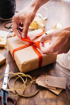 Person, die bogen auf geschenkbox bindet