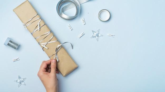 Person, die bogen auf großer geschenkbox bindet