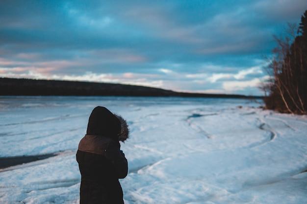 Person, die braune jacke in einem verschneiten feld trägt