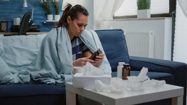 Person, die das etikett einer tablette mit kapseln und einer flasche pillen liest