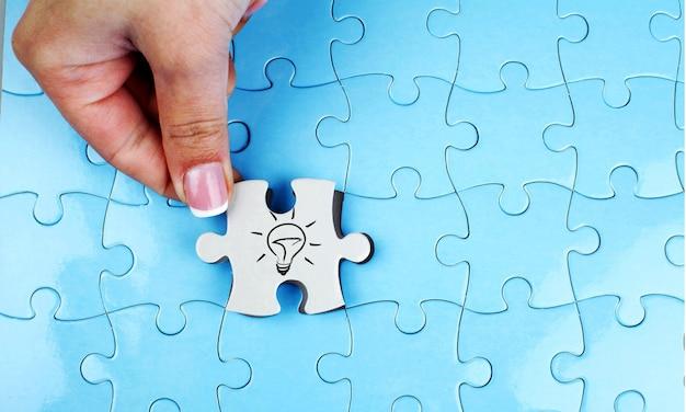 Person, die das letzte puzzleteil anpasst. konzeptbild des gebäudes und des knopfes.