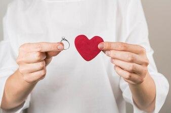 Person, die dekoratives weinartiges Herz und Ring zeigt