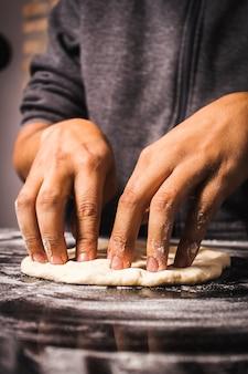 Person, die den teig vorbereitet, um hausgemachte pizza zu machen