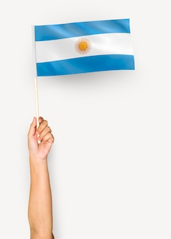Person, die die flagge der argentinien-republik wellenartig bewegt