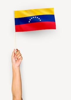 Person, die die flagge der bolivarianischen republik von venezuela wellenartig bewegt