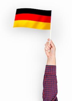 Person, die die flagge der bundesrepublik deutschland weht