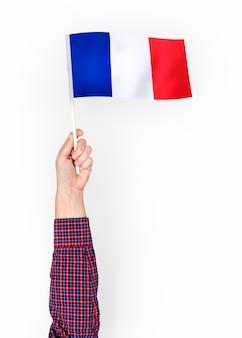Person, die die Flagge der französischen Republik wellenartig bewegt