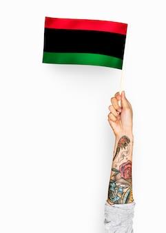 Person, die die flagge der panafrikanischen flagge wellenartig bewegt
