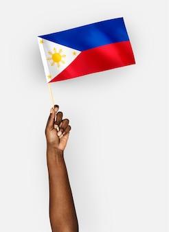 Person, die die flagge der republik der philippinen wellenartig bewegt