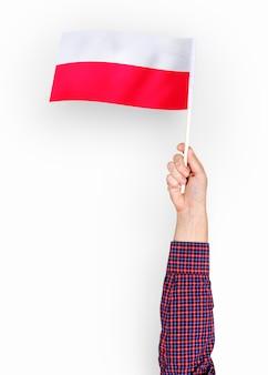 Person, die die flagge der republik von polen wellenartig bewegt