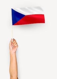 Person, die die flagge der tschechischen republik wellenartig bewegt