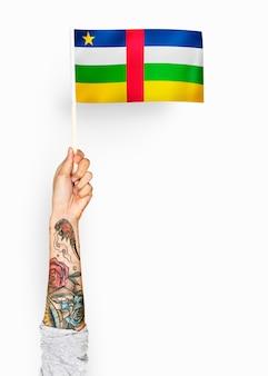 Person, die die flagge der zentralafrikanischen republik wellenartig bewegt