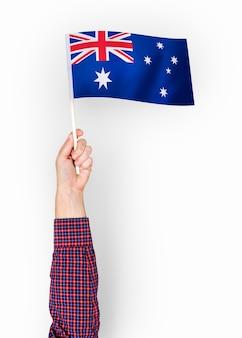 Person, die die flagge des commonwealth von australien wellenartig bewegt