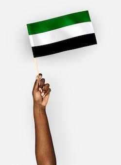 Person, die die flagge des islamischen staates afghanistan wellenartig bewegt