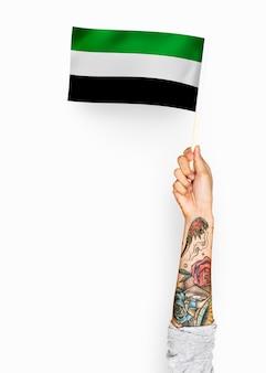 Person, die die flagge des islamischen staates von afghanistan wellenartig bewegt