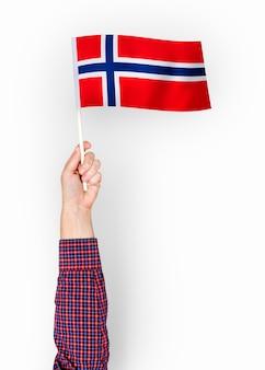 Person, die die flagge des königreichs norwegen wellenartig bewegt