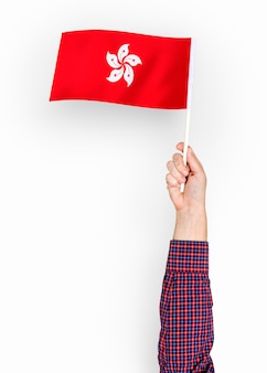 Person, die die flagge von hong kong wellenartig bewegt