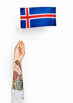 Person, die die flagge von island wellenartig bewegt