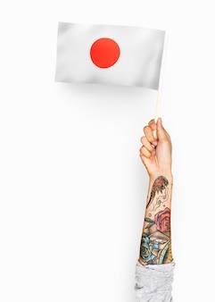 Person, die die flagge von japan wellenartig bewegt