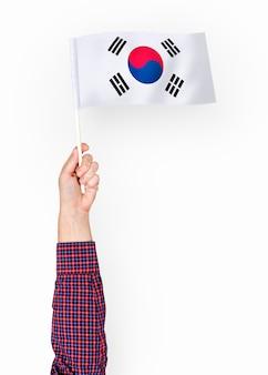 Person, die die flagge von südkorea wellenartig bewegt