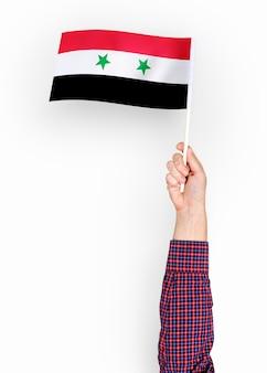 Person, die die flagge von syrien wellenartig bewegt
