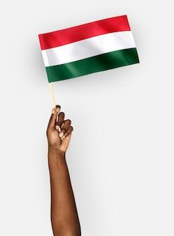 Person, die die flagge von ungarn wellenartig bewegt