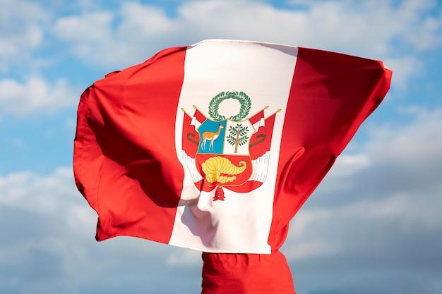 Person, die die peru-flagge im freien hält