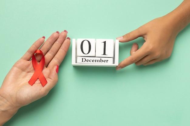 Person, die ein bandsymbol zum welt-aids-tag mit dem ereignisdatum hält