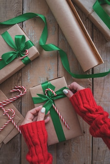 Person, die ein cristmas-geschenk eingewickelt mit kraftpapier, grünem band und zuckerstangen hält