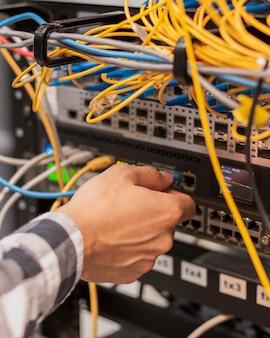 Person, die ein ethernet-kabel an einen netzwerkanschluss anschließt