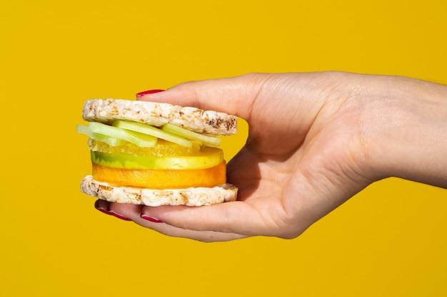 Person, die ein exotisches sandwich mit früchten hält