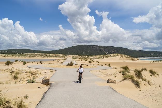 Person, die ein fahrrad durch eine straße, die durch den strand und das meer in andalusien, spanien umgeben ist
