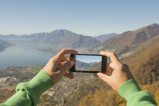 Person, die ein foto des maggiore-alpensees und der berge in der schweiz macht