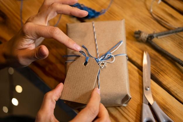 Person, die ein geschenkpapier für ein geschenk macht