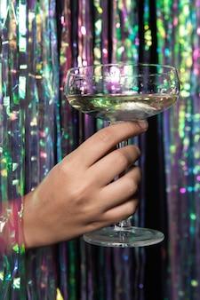 Person, die ein glas der vorderansicht des champagners hält