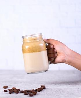 Person, die ein glas karamell-smoothie über kaffeebohnen auf weiß hält