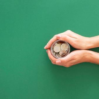Person, die ein glas mit münzen mit kopienraum hält