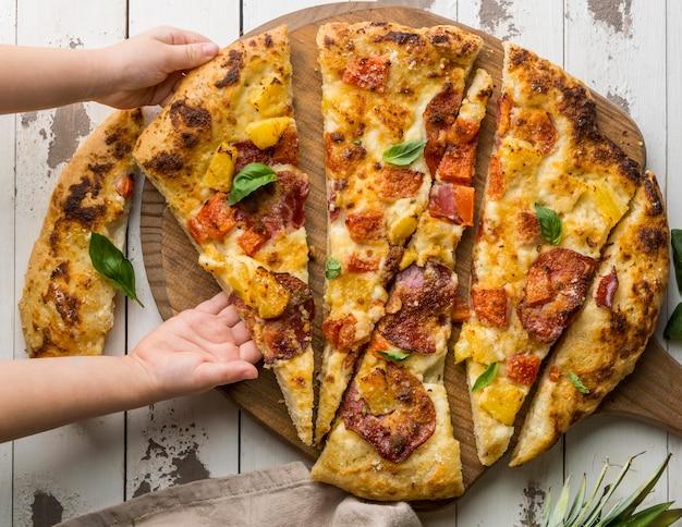 Person, die ein großes stück köstliche gekochte pizza greift